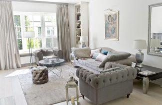 eleganckie wnętrze projektu MIśkiewicz Design salon szara sofa z dwoma szarymi fotelami i błyszcząca pufą