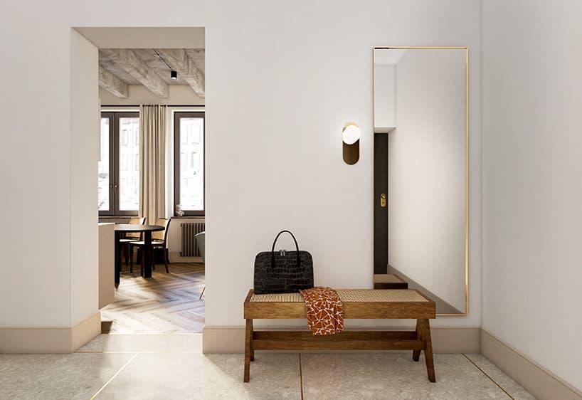 jasny przedpokój zdrewnianą ławką obok wysokiego lustra wzłotej cienkiej ramce
