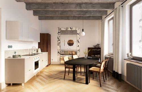 jasna kuchnia z jadalnia z beżową zabudową z czarnym owalnym drewnianym stołem