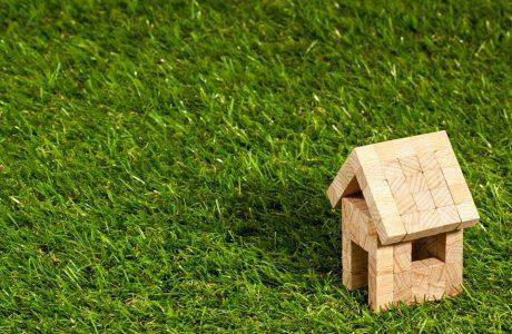 mały domek zabawka z drewnianych klocków na zielonej trawie