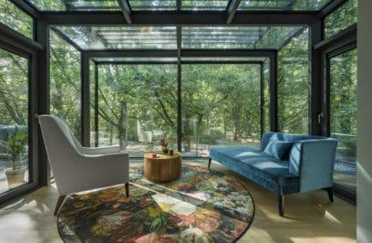 przeszklone atrium z niebieską leżanką i bezowym fotelem na tle drzew