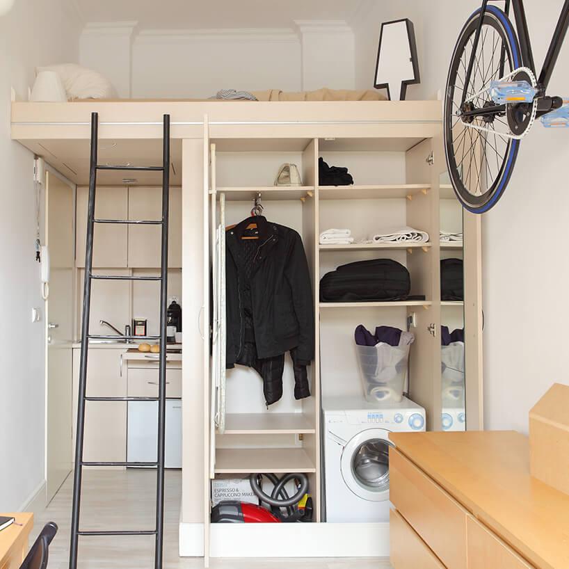 mikromieszkanie 13 mkw projektu Szymona Hanczara otwarta szafa pod andresolą złóżkiem zpralką wśrodku
