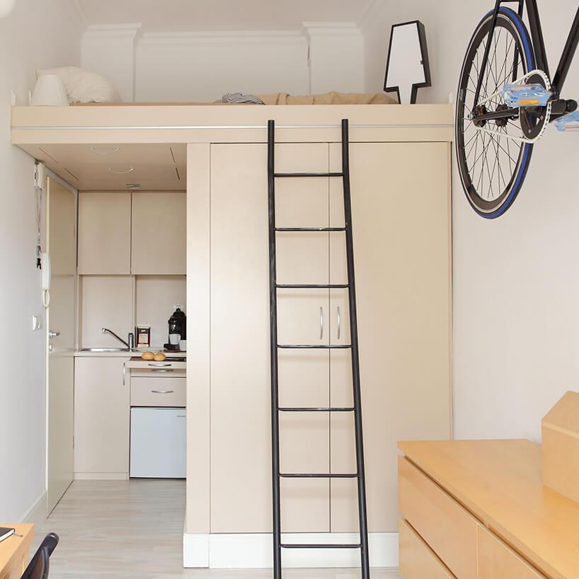 mikromieszkanie 13 mkw projektu Szymona Hanczara czarna drabina oparta obeżową szafę pod antresolą złóżkiem