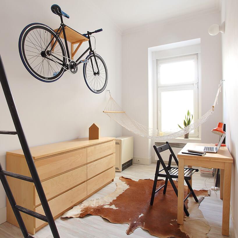 mikromieszkanie 13 mkw projektu Szymona Hanczara rower powieszony nad drewnianą jasną komodą