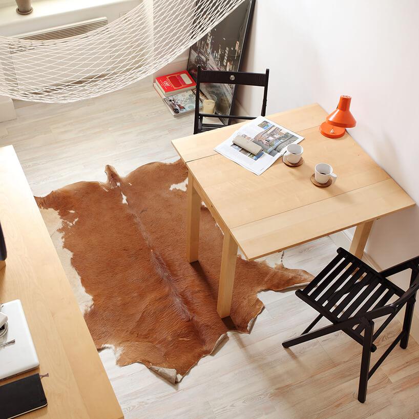 mikromieszkanie 13 mkw projektu Szymona Hanczara widok zantresoli na drewniany rozkładany stolik zczarnym krzesłem