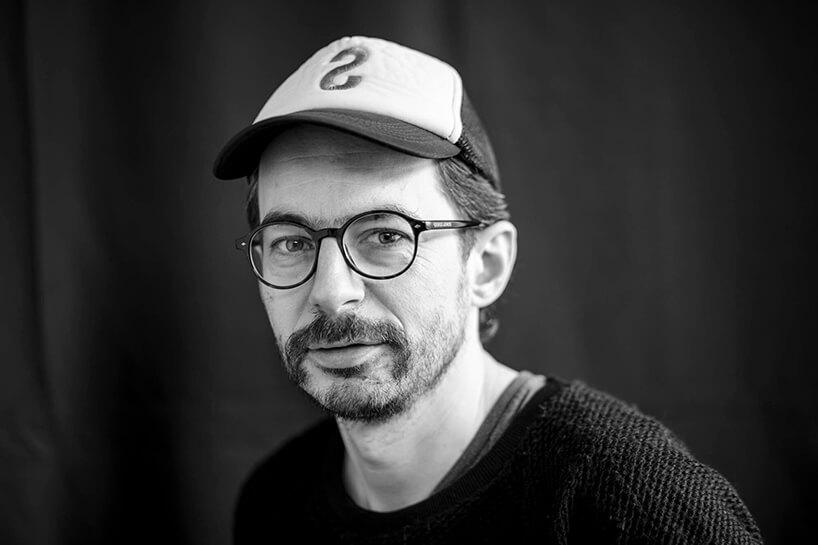 czarno białe zdjęcie projektanta wnętrz Szymona Hanczara wczapce zdaszkiem