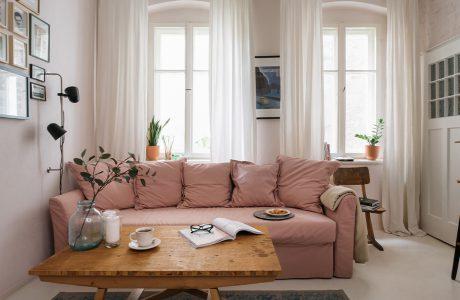 drewniany stolik na tle jasno różowej sofy na tle dwóch wysokich podwójnych okien