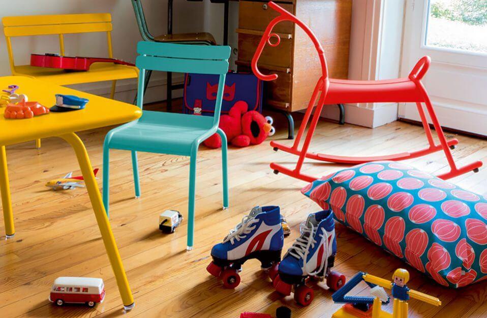kolorowy stolik, krzesła, ławeczka dla dzieci i koń na biegunach w pokoju dziecięcym