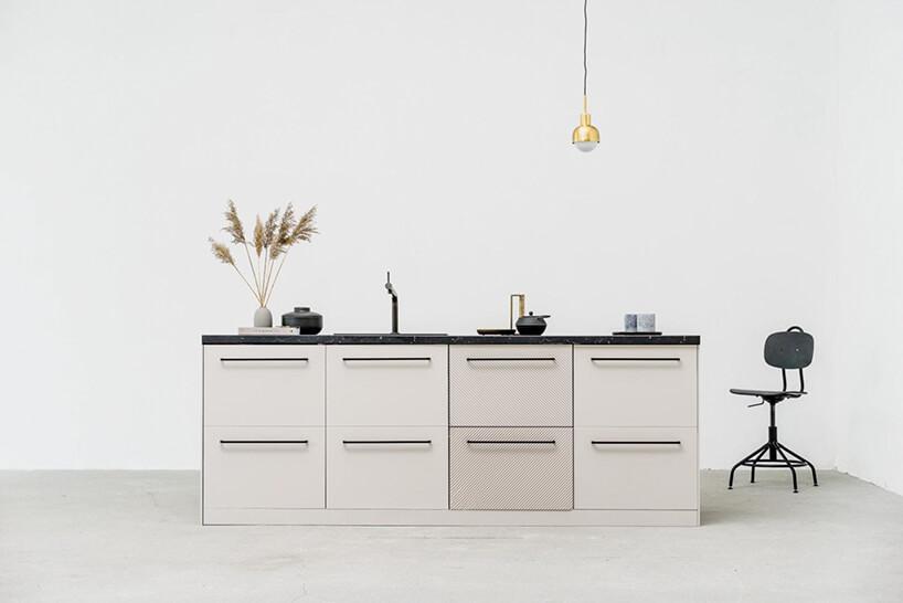 minimalistyczna kuchnia zbiałymi fronatami iczarnym kamiennym blatem