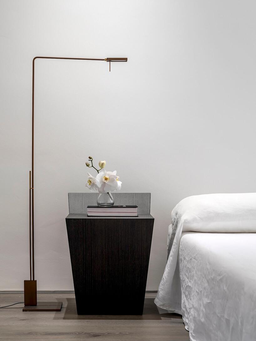 styl minimalistyczny wnętrze sypialni zczarnym stolikiem przy wysokiej lampie