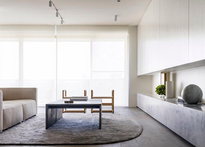 styl minimalistyczny wnętrze salonu zdużą sofą iszarym stolikiem