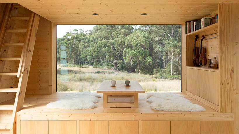 styl minimalistyczny drewniane wnętrze salonu zniskim stolikiem na tle panoramicznego okna zwidokiem na drzewa