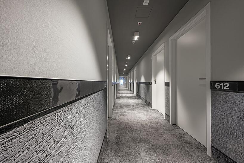 szary nowoczesny korytarz hotelowy zbiałymi drzwiami