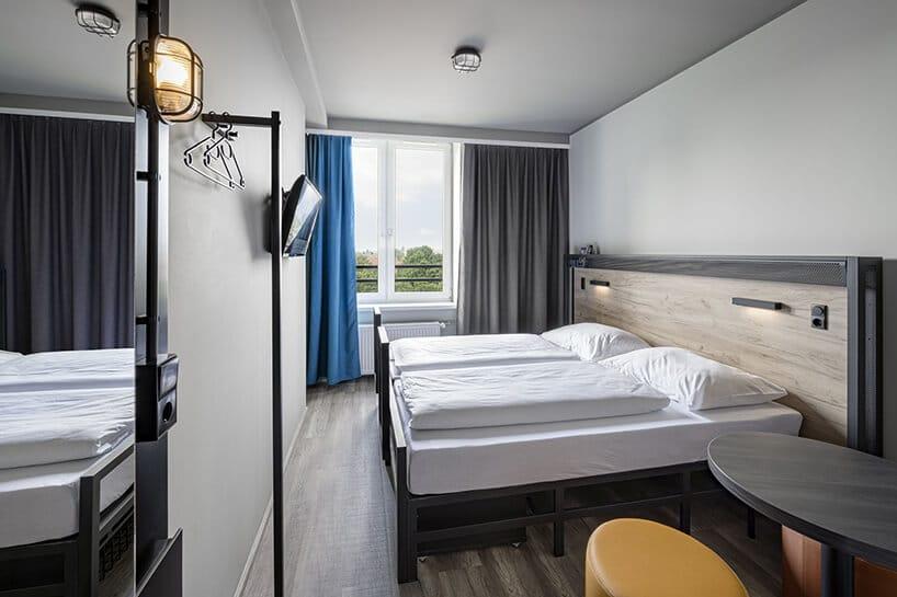 pokój złóżkami przy drewnianym panelu na ścianie oraz zasłonami wkolorze niebieskim iciemno szarym