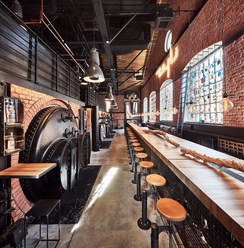 industrialne wnętrze restauracji Zoni projektu Mirosława Nizio długi drewniany stół obok czarnych industrialnych kadzi