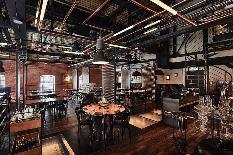 industrialne wnętrze restauracji Zoni projektu Mirosława Nizio drugie piętro zdrewnianą podłogą oszklanymi elementami wpodłodze