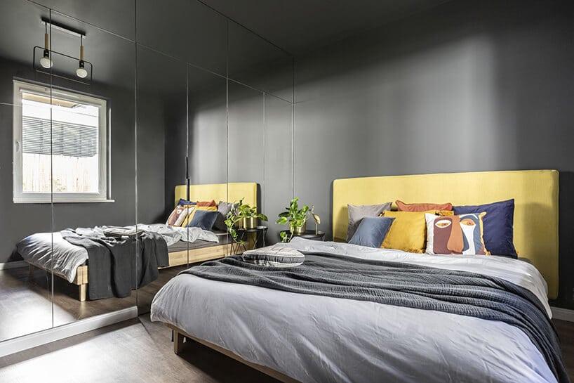 sypialnia wciemnej kolorystyce zdużym lustrem oraz cytrynowo żółtym zagłówkiem ijasno szarymi akcesoriami