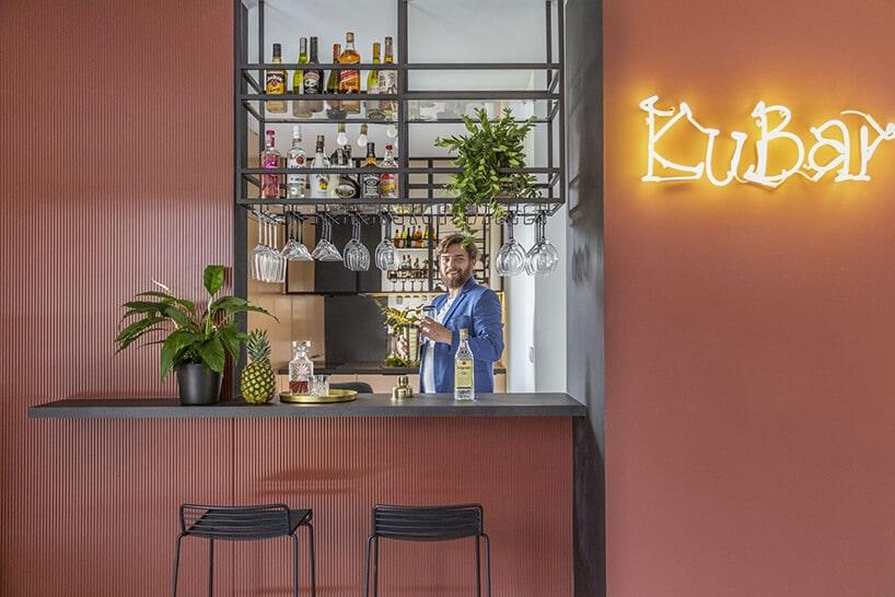 bar wmieszkaniu zbudowany zblachy pomalowanej na ceglastą czerwień zczarnym blatem oraz neonem