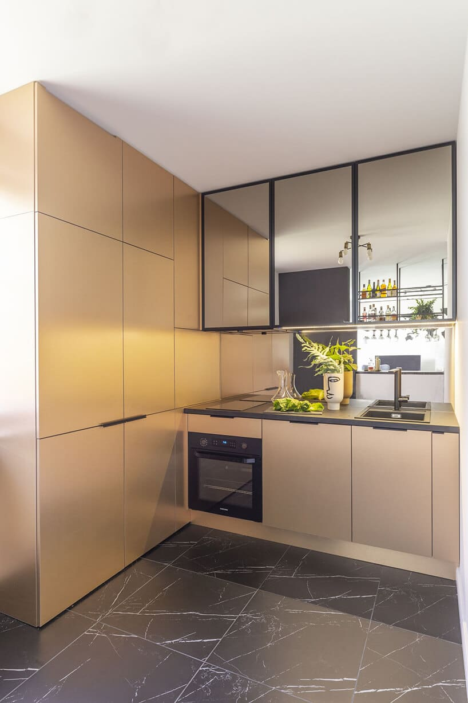 kuchnia zkafelkami imitującymi czarny marmur oraz szafki wkolorze jasnego złota