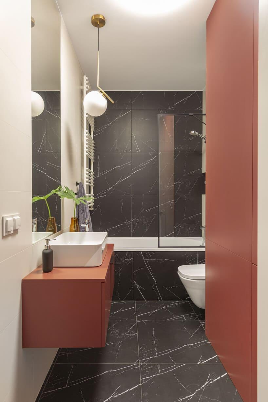łazienka zciemnymi kaflami oraz białą umywalką oraz toaletą iceglastymi szafkami
