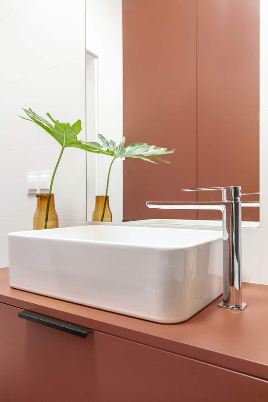 kwadratowa umywalka wbiałym połysku zwysoką chromowaną baterią przy lustrze obok roślinek