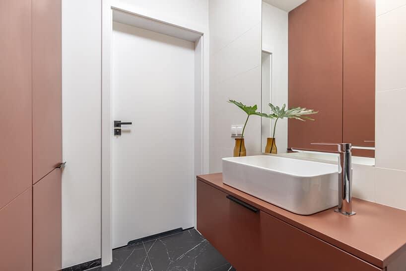białe proste drzwi zczarną klamką włazience zceglastymi szafkami