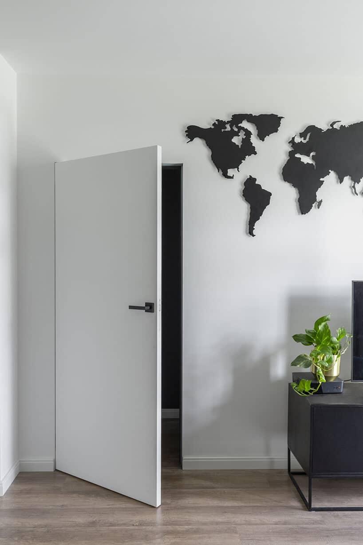 białe drzwi bez framugowe ze ścianą zmapą świata wkolorze czarnym oraz szafeczką zroślina itelewizorem