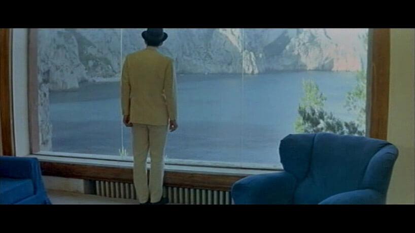 mężczyzna wkapeluszu stojący przed dużym oknem