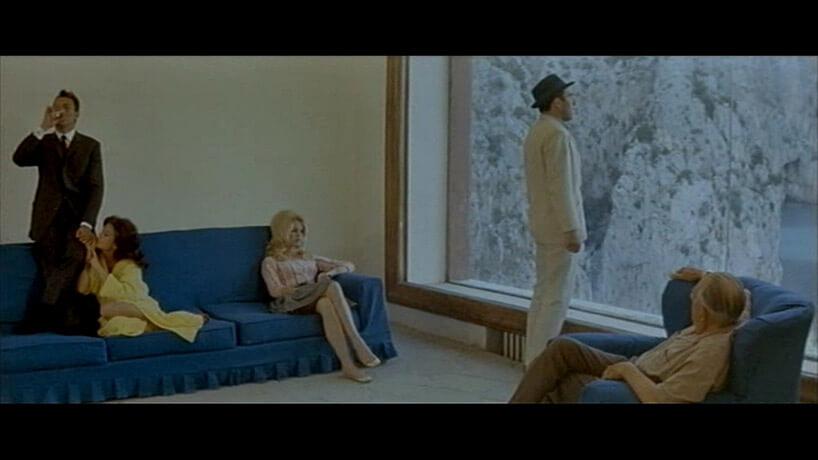 mężczyzna przy oknie ikobieta na niebieskiej sofie