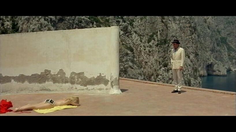 mężczyzna patrzący na opalająca się nago kobietę