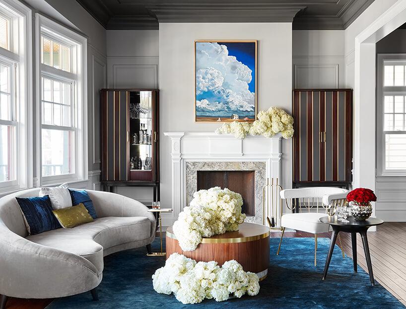 modernistyczne wnętrze Ravenswood Residence elegancki salon zofwalną szarą sofą idużym zdobionym kominkiem