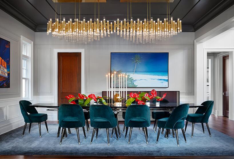 modernistyczne wnętrze Ravenswood Residence elegancka jadalnia zczarnym stołem niebieskim dywanem idwoma złotymi żyrandolami
