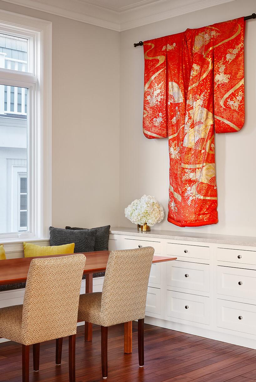modernistyczne wnętrze Ravenswood Residence pomieszcze nie zdrewnianym stołem długa białą szafką ipomarańczowym kimonem zawieszonym na ścianie