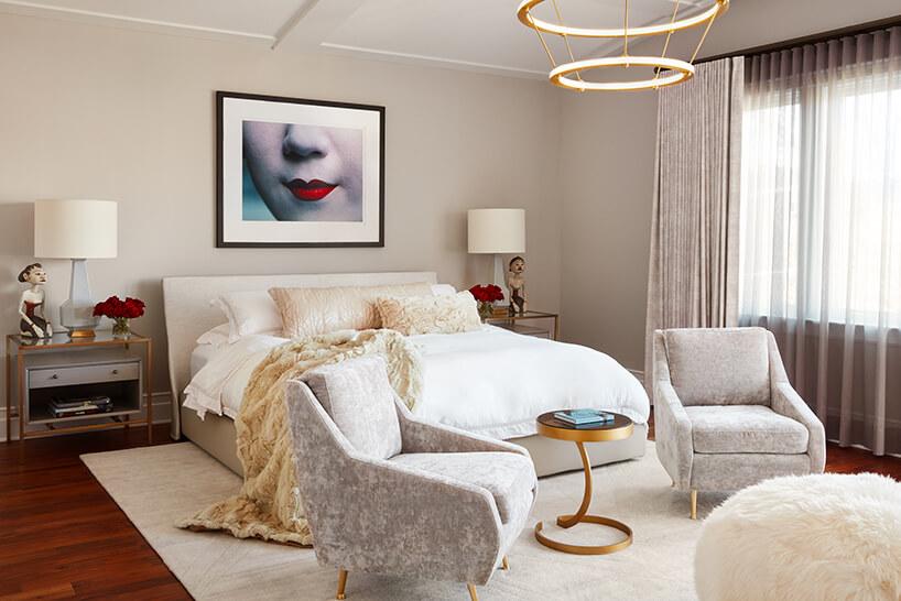 modernistyczne wnętrze Ravenswood Residence elegancka sypialnia zdwoma szarymi fotelami złotymi małym stolikiem ustawionymi przed dużym beżowym łóżkiem