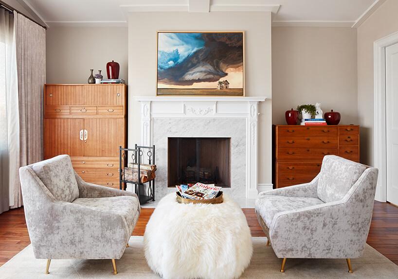 modernistyczne wnętrze Ravenswood Residence elegancki salon ze zdobionym białym kominkiem dwoma szarymi fotelami na złotych nóżkach przy małym pluszowym stoliku