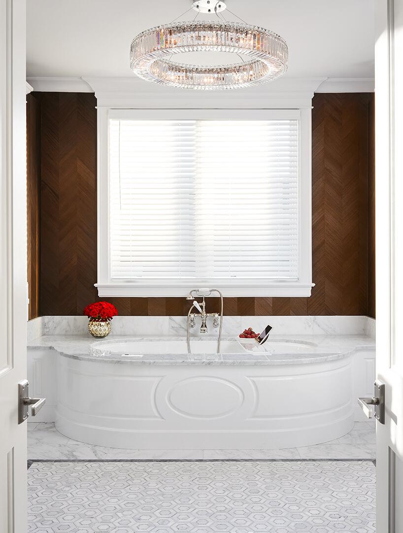 modernistyczne wnętrze Ravenswood Residence ekskluzywna łazienka zwanną osadzoną wbiałym kamieniu ciemnobrązowa drewniana ściana iokrągły żyrandol