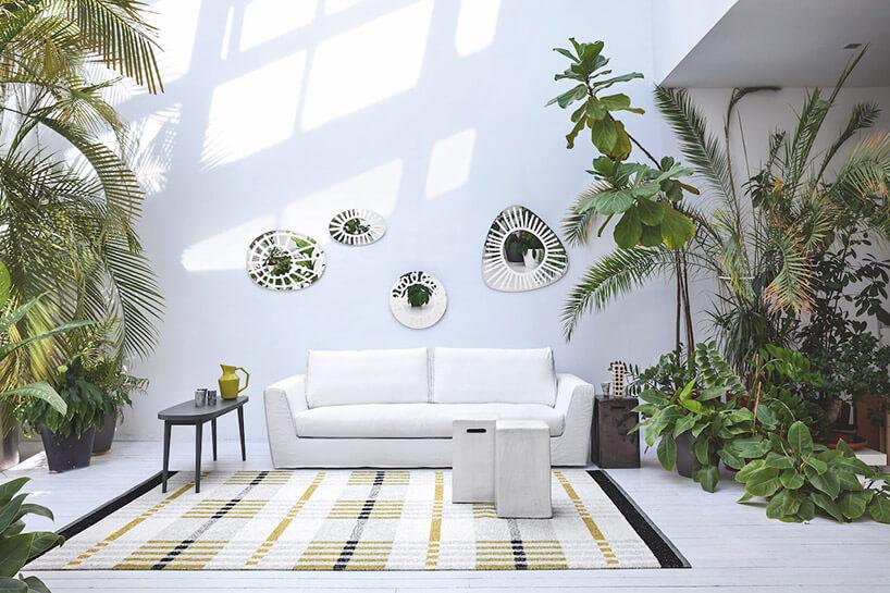 jasne wnętrze zbiałą sofą otoczoną wysokimi roślinami