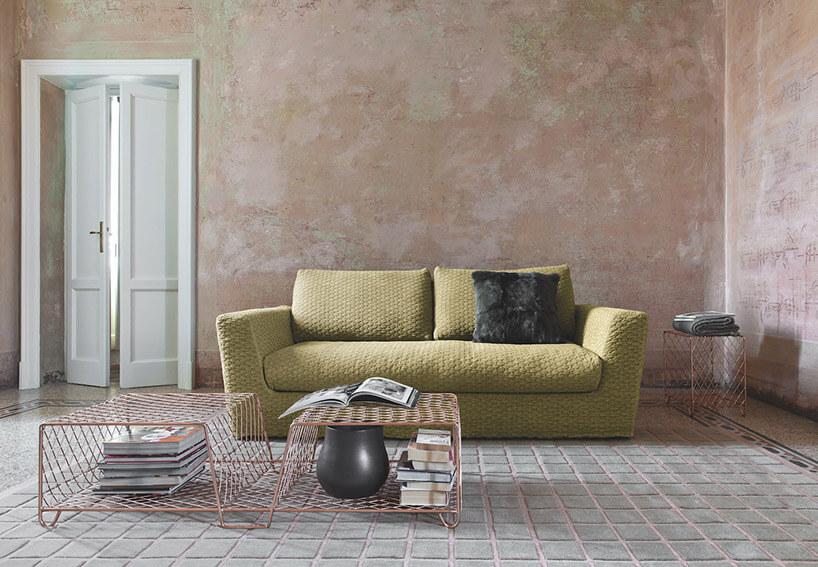 wnętrze zzieloną sofą isiatkowanym stolikiem
