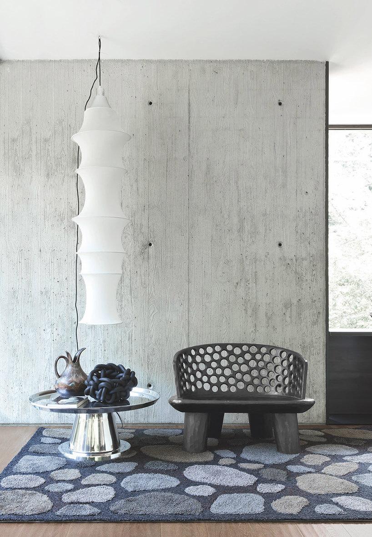 czarny duży niski fotel obok srebrnego stolika idługiem białej lampy wiszącej