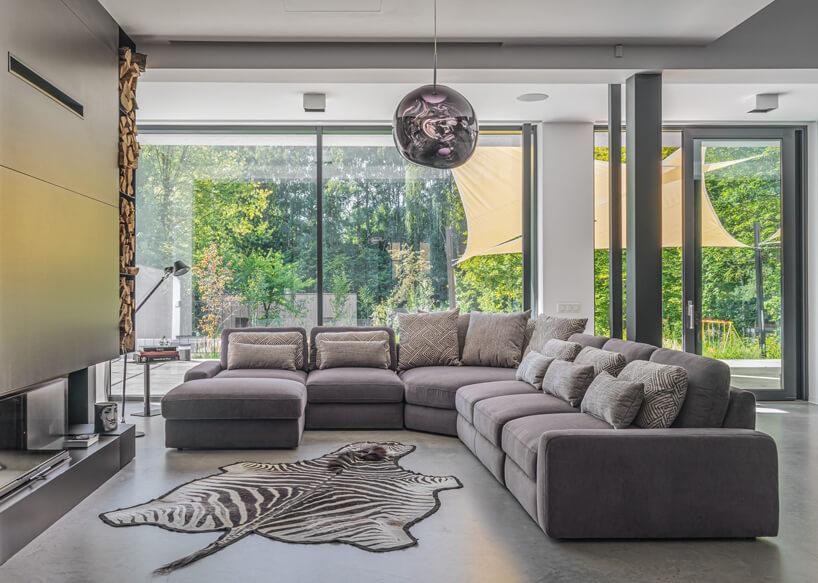 szara modułowa sofa Serena od Gala Collezione wprzestronnym salonie obok skóry zbiałego tygrysa