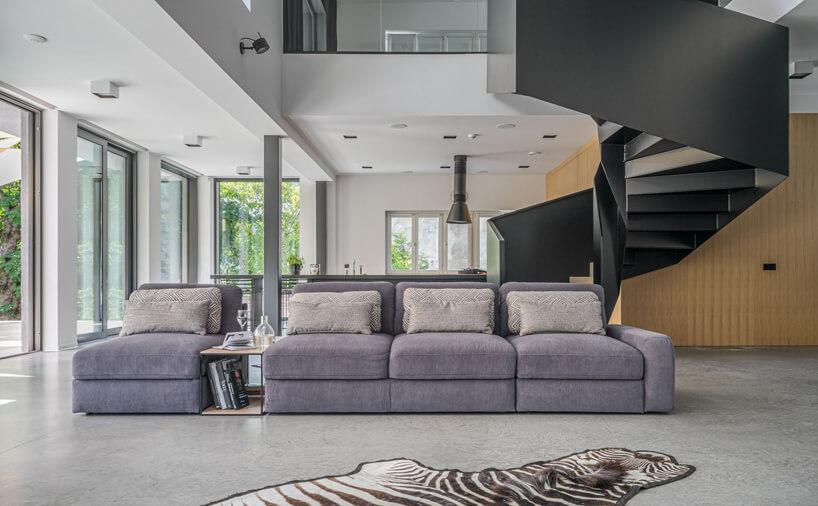 szara modułowa sofa Serena od Gala Collezione wprzestronnym salonie na tle schodów ibiałego piętra