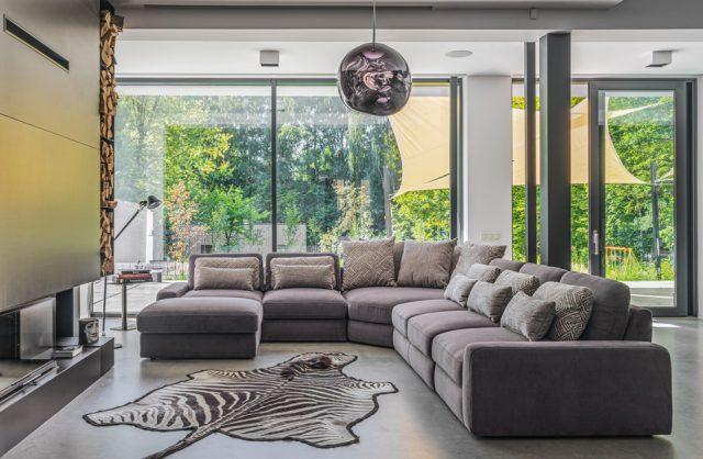 szara modułowa sofa Merida od Gala Collezione w przestronnym salonie obok skóry z białego tygrysa