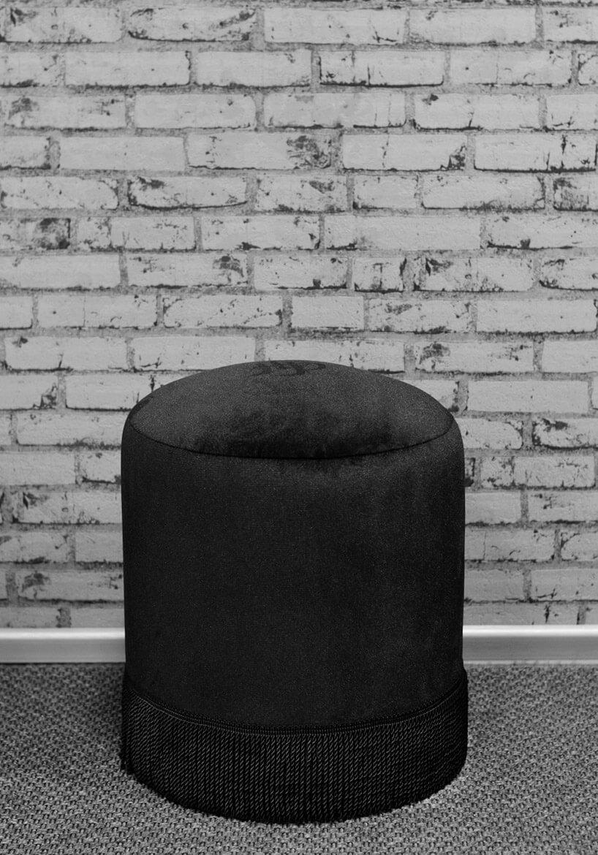 czarna luksusowa pufa na tle ceglanej ściany