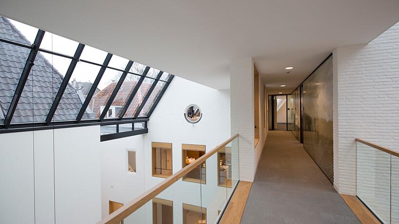 białe wnętrze na wyższym piętrze zdrewnianymi wykończeniami zpochylonym szklanym świetlikiem wdachu