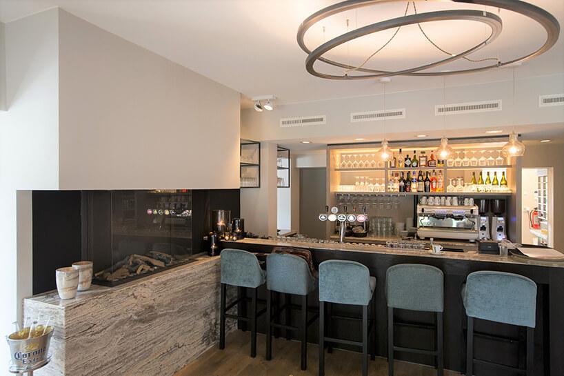 elegancki bar zciemnym wykończeniem zpięcioma krzesłami obok kominka