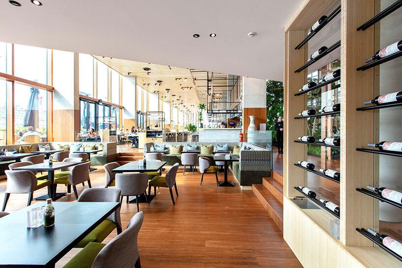 przestrzeń jadalna zdrewnianą podłogą zprzeszkloną ścianą zewnętrzną zczarnymi prostokątnymi iszarymi krzesłami zzielonym siedziskiem