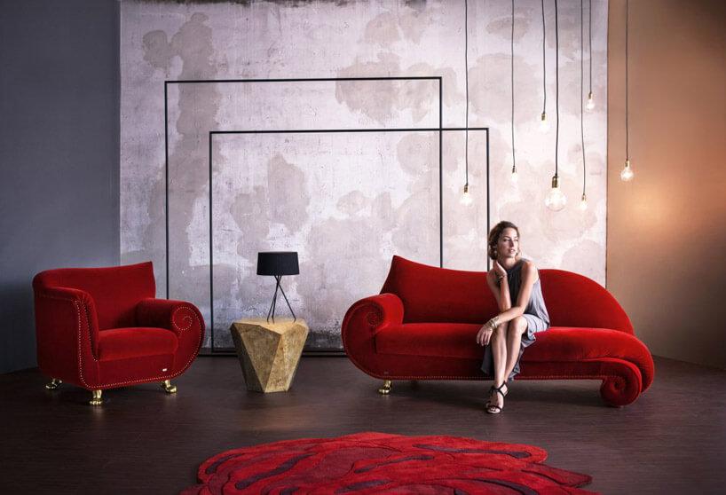 kobieta siedząca na dużej czerwonej sofie wpokoju zinnymi meblami