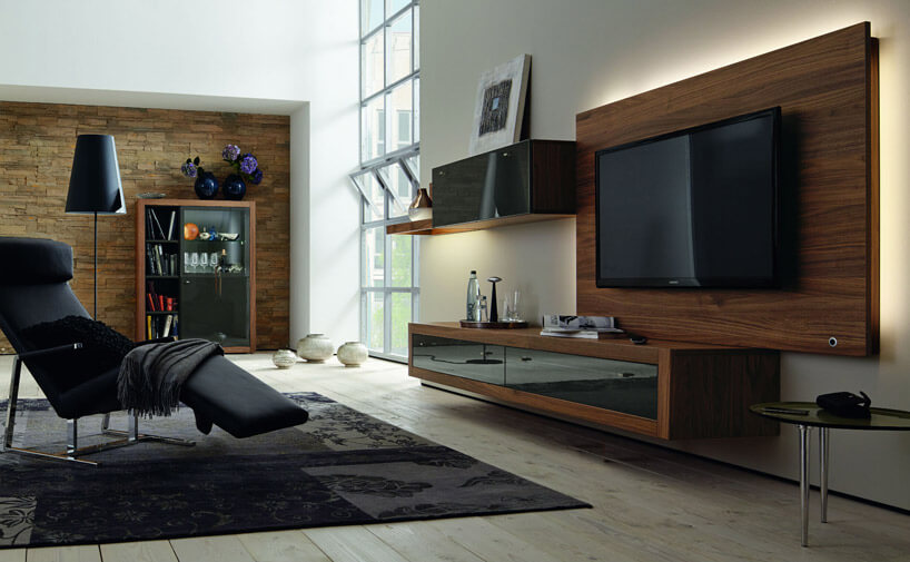 czarny fotel na wzorzystym dywanie wsalonie zdrewnianymi meblami