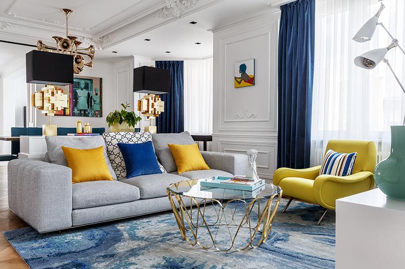 duży biały salon wapartamencie zdrewnianą podłogą zszarą sofą przy szklanym stoliku na złotych nogach