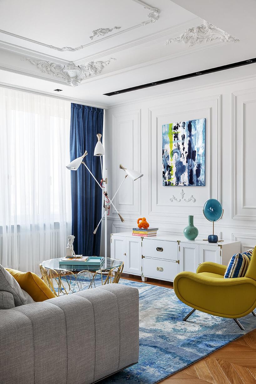 duży biały salon wapartamencie zdrewnianą podłogą zszarą sofą obok żółteo fotela na tle białej niskiej komody